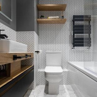 Ispirazione per una stanza da bagno per bambini moderna di medie dimensioni con vasca da incasso, bidè, piastrelle di cemento, pareti grigie, pavimento in cementine, lavabo a bacinella e porta doccia a battente