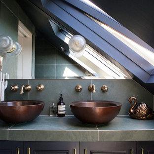 Kleines Modernes Duschbad mit schwarzen Fliesen, schwarzer Wandfarbe, Aufsatzwaschbecken, Schrankfronten mit vertiefter Füllung, schwarzen Schränken, offener Dusche, Wandtoilette mit Spülkasten, Keramikfliesen, Keramikboden, gefliestem Waschtisch, grünem Boden und grüner Waschtischplatte in London