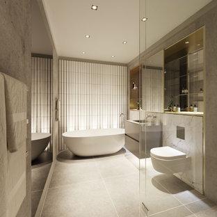 Idéer för att renovera ett mellanstort funkis grå grått en-suite badrum, med släta luckor, grå skåp, ett fristående badkar, en hörndusch, en vägghängd toalettstol, grå kakel, porslinskakel, grå väggar, klinkergolv i porslin, ett integrerad handfat, bänkskiva i glas, grått golv och dusch med gångjärnsdörr