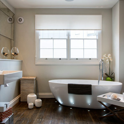 Mid-sized trendy master dark wood floor and brown floor freestanding bathtub photo in London with a wall-mount sink and beige walls