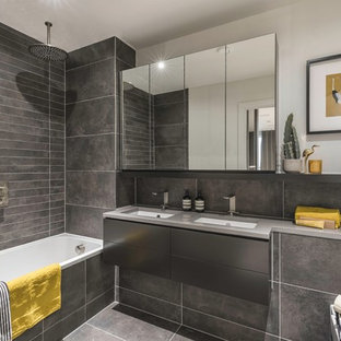This is an example of a contemporary shower room bathroom in London with flat-panel cabinets, grey cabinets, a built-in bath, a shower/bath combination, a wall mounted toilet, grey tiles, grey walls, cement flooring, a submerged sink, concrete worktops, grey floors, an open shower and grey worktops.