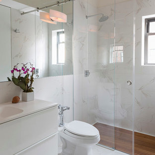 Trendy walk-in shower photo in New York with an integrated sink, flat-panel cabinets, white cabinets, a one-piece toilet and white walls
