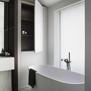 Foto de cuarto de baño principal, actual, grande, con armarios con paneles lisos, puertas de armario azules, sanitario de pared, baldosas y/o azulejos de mármol, paredes amarillas, encimera de mármol, suelo gris y encimeras blancas