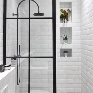 This is an example of an industrial family bathroom in London with a freestanding bath, a walk-in shower, a wall mounted toilet, grey tiles, porcelain tiles, grey walls, cement flooring, a pedestal sink, grey floors and an open shower.