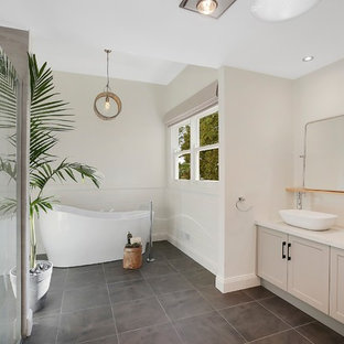 Transitional bathroom in Geelong with shaker cabinets, beige cabinets, a freestanding tub, beige walls, a vessel sink, grey floor and white benchtops.