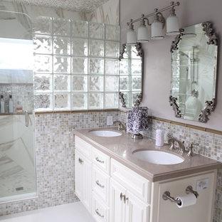 На фото: главная ванная комната среднего размера в классическом стиле с врезной раковиной, фасадами с выступающей филенкой, белыми фасадами, столешницей из искусственного камня, душем в нише, унитазом-моноблоком, разноцветной плиткой, плиткой из листового стекла, серыми стенами и полом из керамогранита с