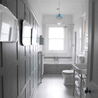 Cette photo montre une salle de bain chic de taille moyenne avec un placard avec porte à panneau encastré, des portes de placard blanches, une baignoire posée, un combiné douche/baignoire, un WC séparé, un carrelage blanc, des carreaux de céramique, un mur vert, sol en stratifié, un sol blanc, une cabine de douche à porte battante et un plan vasque.