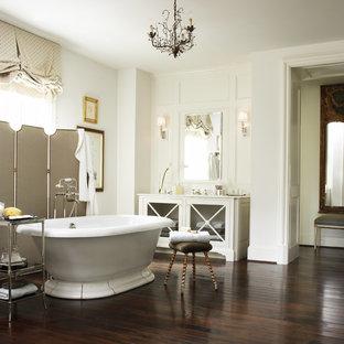 Foto di una stanza da bagno padronale chic di medie dimensioni con vasca freestanding, ante di vetro, ante bianche, pareti bianche, parquet scuro, lavabo sottopiano, top in superficie solida e pavimento marrone