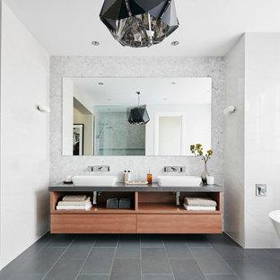 Modern inredning av ett stort badrum, med ett fristående badkar, ett fristående handfat och grått golv