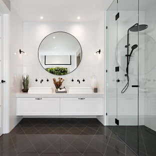This is an example of a mid-sized transitional bathroom in Melbourne with recessed-panel cabinets, white cabinets, a vessel sink, a curbless shower, white walls and a hinged shower door.