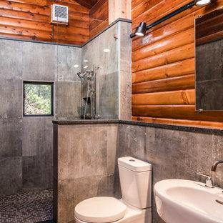 Kleines Rustikales Badezimmer En Suite mit offener Dusche, grauen Fliesen, Zementfliesen, Keramikboden, Sockelwaschbecken, grauem Boden, offener Dusche, Wandtoilette mit Spülkasten, brauner Wandfarbe und Mineralwerkstoff-Waschtisch in Seattle