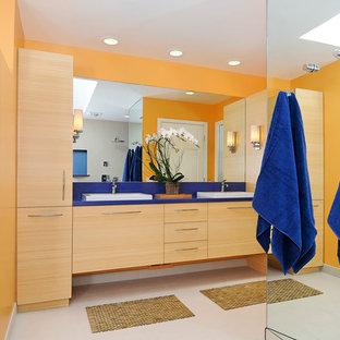 Diseño de cuarto de baño contemporáneo con lavabo encastrado, armarios con paneles lisos, puertas de armario de madera clara, parades naranjas y encimeras azules