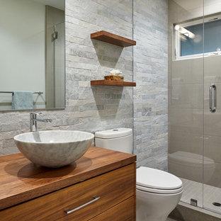 Ispirazione per una piccola stanza da bagno contemporanea con ante lisce, ante in legno scuro, WC a due pezzi, piastrelle verdi, piastrelle in pietra, pareti verdi, pavimento in pietra calcarea, lavabo a bacinella e top in legno