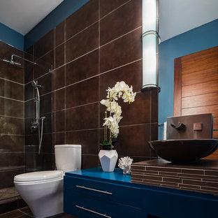 サンフランシスコの中サイズのモダンスタイルのおしゃれなバスルーム (浴槽なし) (家具調キャビネット、茶色いキャビネット、コーナー設置型シャワー、一体型トイレ、茶色いタイル、セラミックタイル、青い壁、セラミックタイルの床、コンソール型シンク、タイルの洗面台、茶色い床、引戸のシャワー、ブラウンの洗面カウンター) の写真