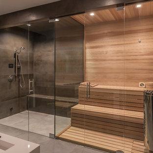 サンフランシスコの巨大なモダンスタイルのおしゃれなサウナ (白いキャビネット、ダブルシャワー、壁掛け式トイレ、黒いタイル、セラミックタイル、黒い壁、セラミックタイルの床、壁付け型シンク、黒い床、開き戸のシャワー、白い洗面カウンター) の写真