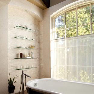 Modelo de cuarto de baño principal, mediterráneo, grande, con armarios abiertos, encimera de vidrio, bañera exenta, baldosas y/o azulejos beige, paredes beige y baldosas y/o azulejos de vidrio