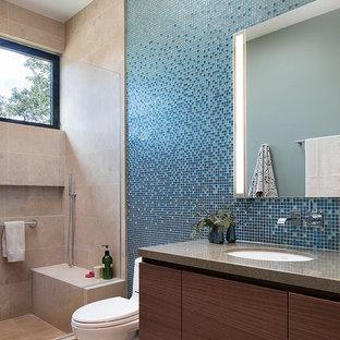 Ispirazione per una stanza da bagno per bambini minimal di medie dimensioni con ante lisce, ante in legno bruno, doccia alcova, WC monopezzo, piastrelle blu, piastrelle di vetro, pavimento in pietra calcarea, lavabo sottopiano, top in quarzo composito, pavimento beige e top marrone