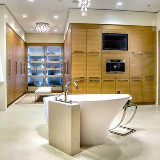Ejemplo de cuarto de baño actual con bañera exenta, encimera de granito, lavabo sobreencimera, armarios con paneles lisos y puertas de armario de madera clara
