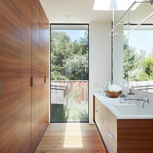 Источник вдохновения для домашнего уюта: ванная комната в стиле ретро с плоскими фасадами, фасадами цвета дерева среднего тона, белыми стенами, светлым паркетным полом, монолитной раковиной и белой столешницей