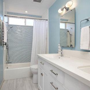 Ejemplo de cuarto de baño infantil, actual, de tamaño medio, con armarios con paneles empotrados, puertas de armario blancas, bañera empotrada, combinación de ducha y bañera, sanitario de dos piezas, baldosas y/o azulejos azules, baldosas y/o azulejos de vidrio laminado, paredes azules, suelo de baldosas de porcelana, lavabo bajoencimera, encimera de cuarzo compacto, suelo gris y ducha con cortina