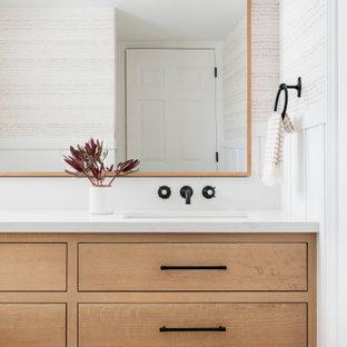 Bild på ett litet lantligt vit vitt badrum, med luckor med profilerade fronter, skåp i ljust trä, en toalettstol med separat cisternkåpa, vita väggar, cementgolv, ett undermonterad handfat, bänkskiva i kvarts och vitt golv