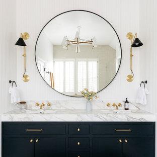 Идея дизайна: большая главная ванная комната в стиле кантри с фасадами с декоративным кантом, синими фасадами, ванной на ножках, душем без бортиков, раздельным унитазом, белой плиткой, керамической плиткой, белыми стенами, полом из цементной плитки, врезной раковиной, мраморной столешницей, белым полом, душем с распашными дверями, белой столешницей, унитазом, тумбой под две раковины, встроенной тумбой, сводчатым потолком и панелями на части стены