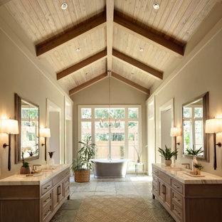 Aménagement d'une salle de bain principale campagne avec une baignoire indépendante, un mur beige, un sol en calcaire, meuble-lavabo sur pied, un plafond en poutres apparentes, un plafond voûté, un plafond en bois, un placard à porte affleurante, des portes de placard en bois brun, un lavabo encastré, un sol gris, un plan de toilette blanc et meuble double vasque.