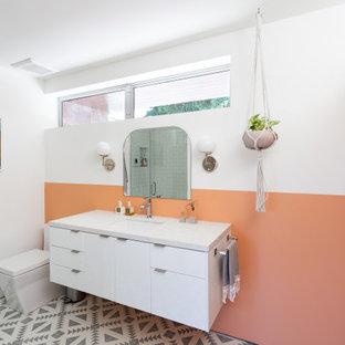 Imagen de cuarto de baño actual con armarios con paneles lisos, puertas de armario blancas, parades naranjas, lavabo bajoencimera, suelo multicolor y encimeras blancas