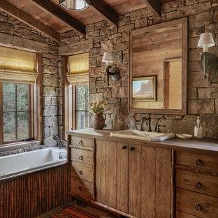 Cette image montre une salle de bain principale chalet avec un placard en trompe-l'oeil, des portes de placard en bois brun, une baignoire posée, un lavabo posé et un plan de toilette gris.