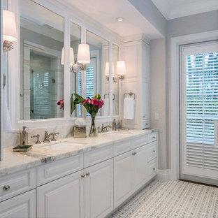 Réalisation d'une grand salle de bain principale tradition avec un placard avec porte à panneau surélevé, une baignoire encastrée, un WC à poser, un mur gris, un sol en carrelage de terre cuite, un lavabo encastré, un plan de toilette en marbre, une cabine de douche à porte battante, un plan de toilette blanc, des portes de placard violettes et un sol blanc.