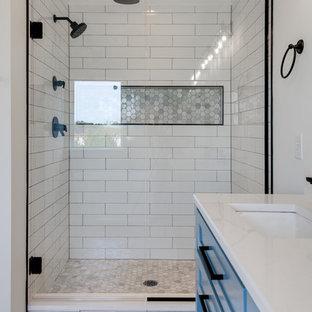 Immagine di una grande stanza da bagno padronale country con consolle stile comò, ante blu, vasca freestanding, doccia alcova, pareti bianche, pavimento con piastrelle in ceramica, lavabo sottopiano, top in quarzite, pavimento bianco, porta doccia a battente e top bianco