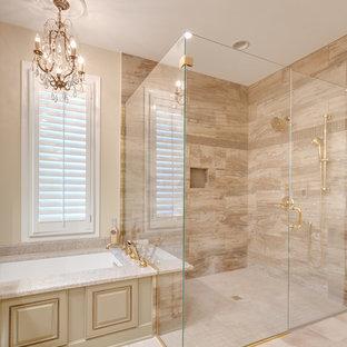 Inredning av ett klassiskt stort beige beige en-suite badrum, med ett undermonterad handfat, luckor med upphöjd panel, granitbänkskiva, ett undermonterat badkar, en hörndusch, en toalettstol med separat cisternkåpa, beige kakel, porslinskakel, beige väggar, klinkergolv i porslin, gröna skåp, beiget golv och dusch med gångjärnsdörr