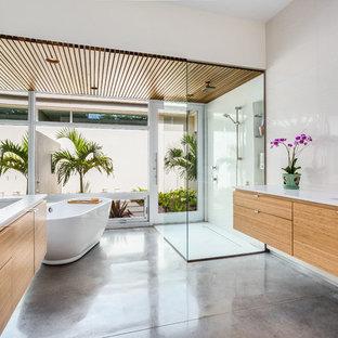 Inspiration för exotiska en-suite badrum, med ett undermonterad handfat, släta luckor, skåp i mellenmörkt trä, bänkskiva i kvarts, ett fristående badkar, en kantlös dusch, vit kakel, betonggolv, beige väggar och grått golv