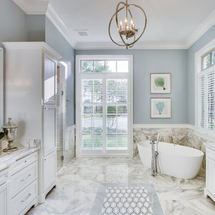 Elegant master multicolored tile multicolored floor freestanding bathtub photo in New Orleans with recessed-panel cabinets, white cabinets, blue walls and multicolored countertops