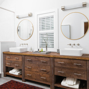 Example of a cottage master white tile gray floor alcove shower design in Boston with furniture-like cabinets, medium tone wood cabinets, white walls, a vessel sink, wood countertops, a hinged shower door and brown countertops