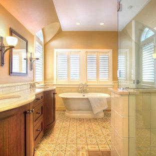 Diseño de cuarto de baño principal, marinero, con armarios con rebordes decorativos, puertas de armario marrones, bañera exenta, ducha esquinera, baldosas y/o azulejos grises, baldosas y/o azulejos de cerámica, paredes beige, suelo de azulejos de cemento, lavabo bajoencimera, encimera de cuarzo compacto, suelo amarillo y ducha con puerta con bisagras