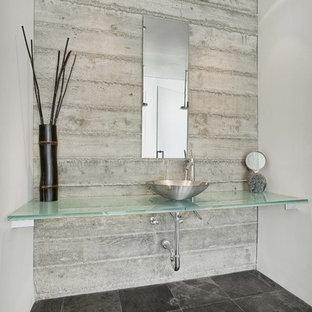Diseño de cuarto de baño contemporáneo con lavabo sobreencimera, suelo negro y encimeras turquesas
