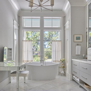 Design ideas for a large transitional master bathroom in Charleston with flat-panel cabinets, grey cabinets, a freestanding tub, gray tile, glass tile, grey walls, marble floors, an undermount sink, marble benchtops, white floor and white benchtops.
