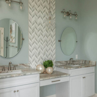 Inspiration for a large coastal master beige tile and stone tile bathroom remodel in Atlanta with recessed-panel cabinets, white cabinets, green walls, an undermount sink and multicolored countertops