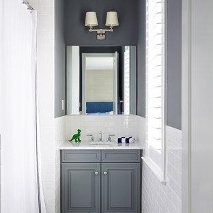 Ejemplo de cuarto de baño infantil, clásico, pequeño, con lavabo bajoencimera, armarios con paneles con relieve, puertas de armario grises, ducha empotrada, baldosas y/o azulejos blancos, baldosas y/o azulejos de cemento y paredes grises