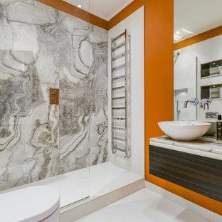 Modelo de cuarto de baño con ducha, contemporáneo, de tamaño medio, con armarios con paneles lisos, puertas de armario de madera en tonos medios, ducha empotrada, sanitario de pared, baldosas y/o azulejos grises, baldosas y/o azulejos blancos, parades naranjas, suelo de baldosas de porcelana, lavabo sobreencimera, suelo blanco y encimeras grises