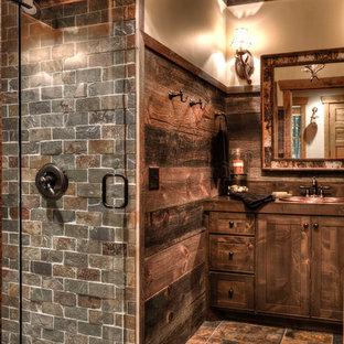 ミネアポリスのラスティックスタイルのおしゃれな浴室 (濃色木目調キャビネット、木製洗面台、オーバーカウンターシンク、シェーカースタイル扉のキャビネット、アルコーブ型シャワー、茶色いタイル、ベージュの壁、茶色い床、スレートタイル、ブラウンの洗面カウンター) の写真