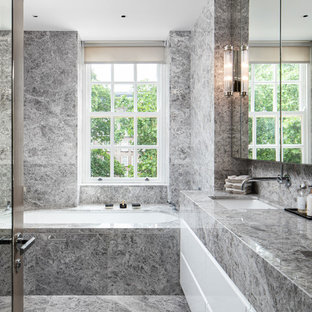 Contemporary bathroom in Surrey with flat-panel cabinets, white cabinets, a submerged bath, a submerged sink, grey floors and grey worktops.
