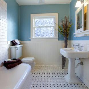 Inredning av ett amerikanskt mellanstort badrum med dusch, med ett fristående badkar, en toalettstol med separat cisternkåpa, vit kakel, tunnelbanekakel, blå väggar, klinkergolv i keramik, ett piedestal handfat och flerfärgat golv
