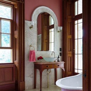 Foto di una grande stanza da bagno padronale tradizionale con ante marroni, vasca con piedi a zampa di leone, piastrelle beige, piastrelle in pietra, pareti rosa, pavimento in marmo, lavabo a bacinella e top in marmo