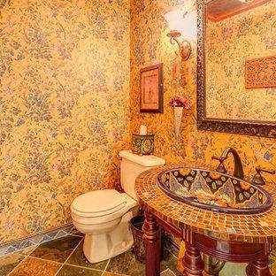 Imagen de cuarto de baño bohemio, pequeño, con lavabo encastrado, puertas de armario con efecto envejecido, encimera de azulejos, sanitario de dos piezas, baldosas y/o azulejos de vidrio, paredes multicolor y suelo de pizarra