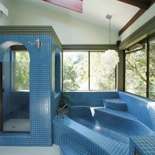 Eklektisk inredning av ett badrum, med en dusch i en alkov, blå kakel och mosaik