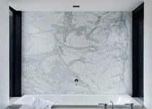 Please advse:  is this wall behind the bath one piece of marble?