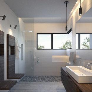 На фото: большая главная ванная комната в восточном стиле с плоскими фасадами, фасадами цвета дерева среднего тона, открытым душем, унитазом-моноблоком, белой плиткой, галечной плиткой, белыми стенами, полом из керамогранита, раковиной с пьедесталом и столешницей из дерева