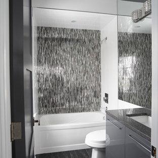 Imagen de cuarto de baño con ducha, minimalista, pequeño, con puertas de armario grises, bañera empotrada, combinación de ducha y bañera, sanitario de dos piezas, baldosas y/o azulejos negros, baldosas y/o azulejos grises, azulejos en listel, paredes grises, suelo de baldosas de porcelana, lavabo bajoencimera, encimera de granito, armarios con paneles lisos y encimeras grises